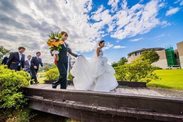 橋を歩いて渡るドレス姿の花嫁