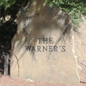 """This is a photo of a rock marker by a driveway. It reads, """"The Warner's."""""""