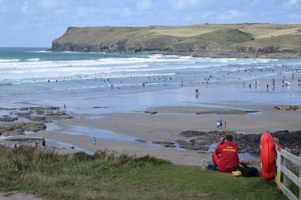 View of surf rolling in at Polzeath beach from the cliff top. Lots of people in the sea and a lifeguard in the foreground looking out for them.