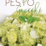 white bowl of creamy pesto gnocchi with shaved parmesan and basil leaf