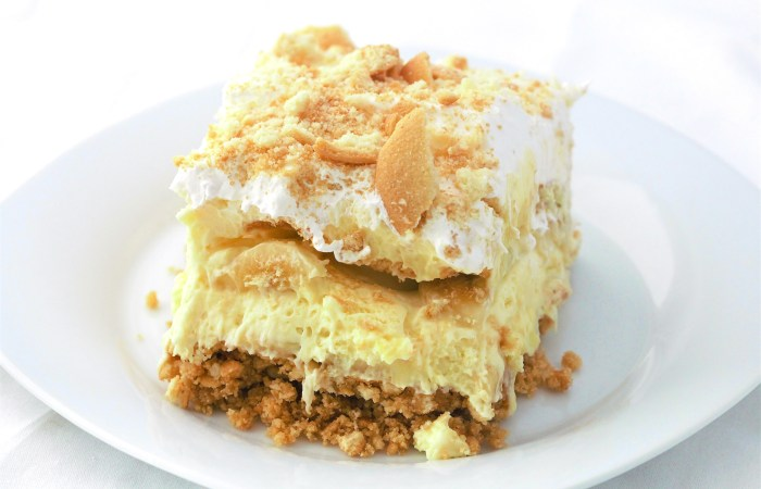 a slice of banana pudding pie with vanilla wafer on top on a white plate