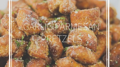 a white bowl of garlic parmesan pretzel nuggets with parmesan sprinkled on top