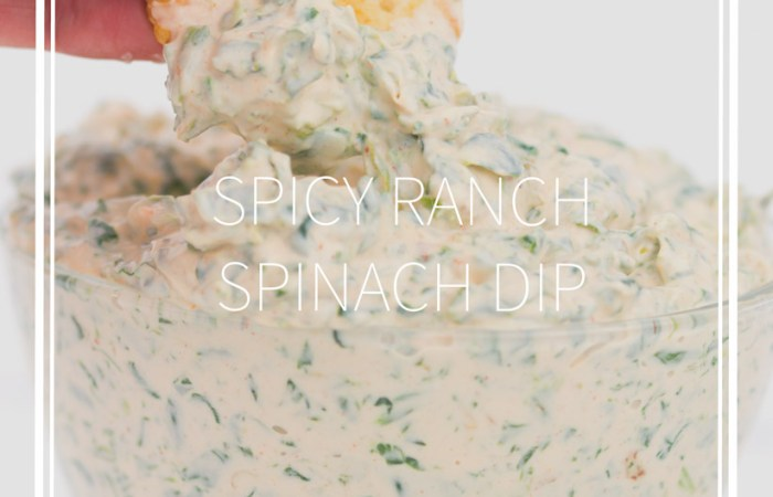 a glass bowl with spicy ranch spinach dip in it dipping a cracker in the dip