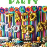 streamer back drop with mexican flowers border wih taco twosday balloons with mexican food table with title