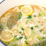 large pot of homemade chicken noodle soup with parsley, bay leaves, and sliced lemons