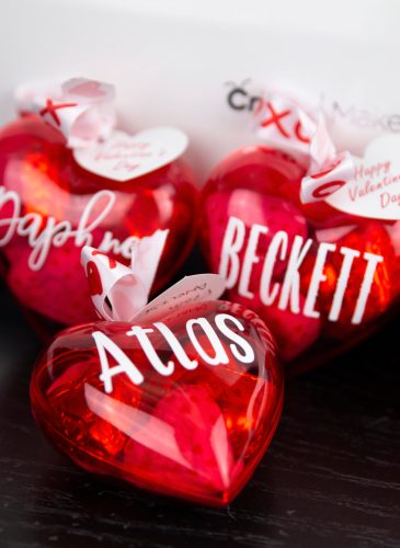 3 plastic red hearts filled with candy with names on them and ribbon on top