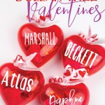 4 plastic red hearts filled with candy with names on them and ribbon on top
