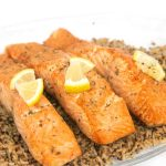 a glass plate of easy air fryer salmon pieces on top of brown rice with lemon on top of the salmon