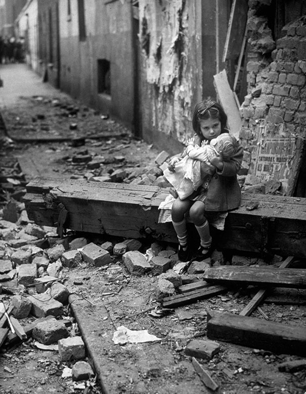Little girl with her doll sitting in the ruins of her bombed home, London, 1940.