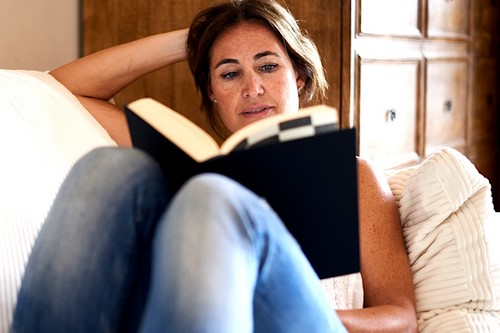 Mature woman reading a book in her sofa