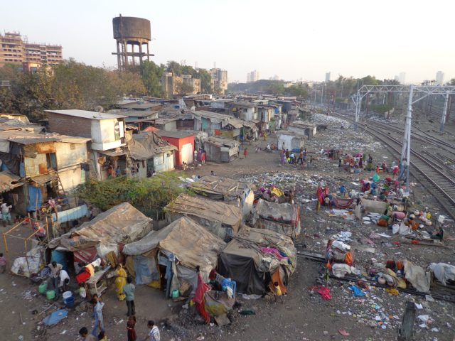 houses in dharavi slum are built right up to the railway tracks