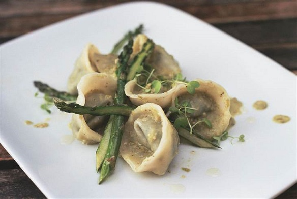 A delicious serving of pipián pesto tortellini with seared asparagus and roasted tomatillo sauce. Photo Credit: Merida Anderson