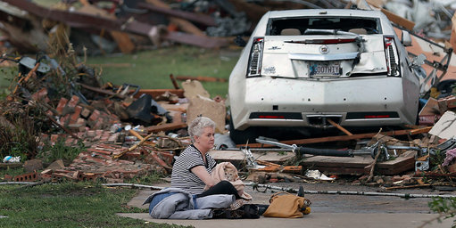 Kay James holding her cat amid the ruins of their home. Photo Credit: Chris Landsberger, Oklahoman, via Associated Press