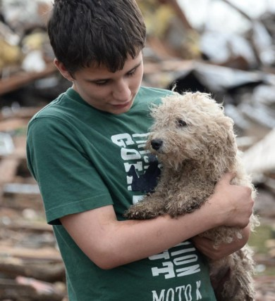 A boy cradles his dog among the rubble in Moore, Okla., Monday, May 20, 2013. Photo Credit: Gene Blevins / ZUMAPRESS.com