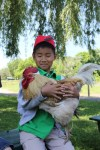 student holds rooster at catskill animal sanctuary
