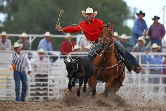Riley Pruitt of Gering, Neb. competes in calf roping during a Cheyenne Frontier Days rodeo at Frontier Park. Photo Credit: Andrew Carpenean, US Presswire
