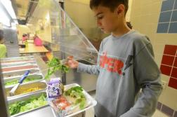 Thomas Gafaro, 8, a third-grader at P.S. 244, helps himself to some salad./Photo credit: NY Daily News, Aaron Showalter