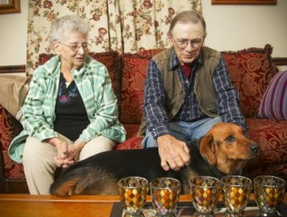 Edna and James Gross, with one of their two dogs, Trouble, in their Williamsdale home. The Grosses get Meals on Wheels delivered by Partners in Prime. The organization also provides pet food to clients so that they do not share their daily meals with their pets. Photo Credit: Greg Lynch