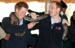 prince harry and prince william holding a python snake