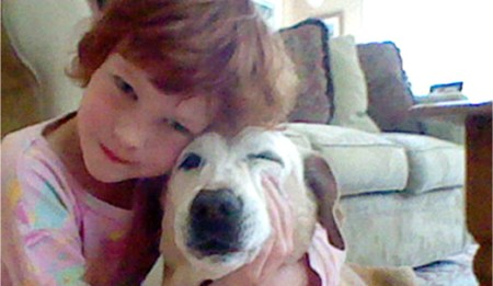 Catherine Violet Hubbard hugging her dog Sammy at their home in Newtown, CT. The 6-year-old was tragically killed on December 14, 2012 in the Sandy Hook Elementary School mass shooting./Photo credit:cvhfoundation.org