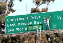 Steve-o, an animal rights activist, poses in front of the SeaWorld freeway sign Photo credit: Discoversd.com