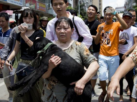 An animal rights activist carries a dog she bought at a market in Yulin. Photo Credit: AP