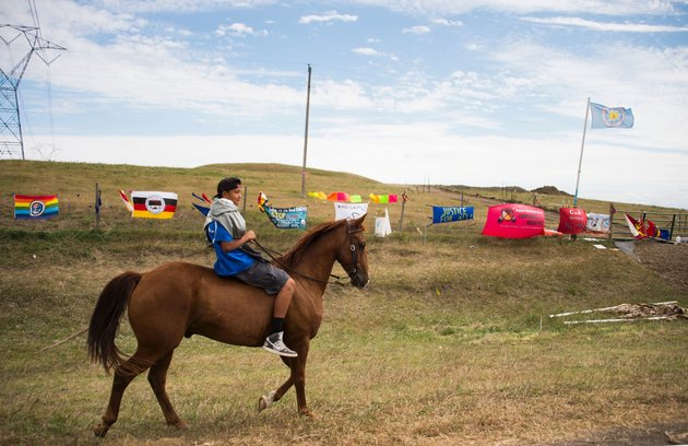 A young man rides a horse over a fenced area of land set aside for the Dakota Access Pipeline in North Dakota. Photo Credit: Robyn Beck, AFP/Getty Images