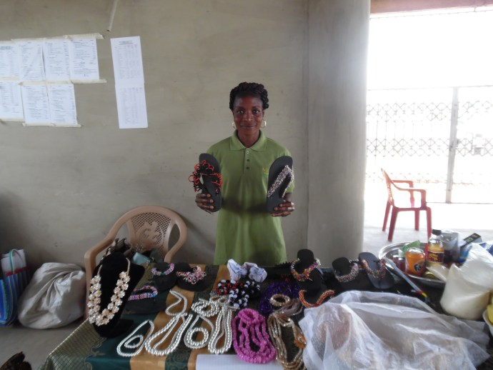 Sandra holds a pair of Charlie sandals and stands behind her beaded products
