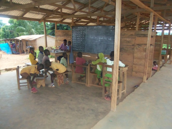children gather in a classroom with new concrete floors