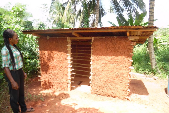young girl stands in front of the new latrine at Beposo School