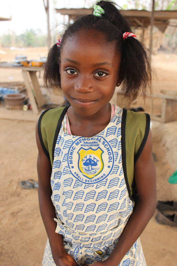 young girl stands smiling