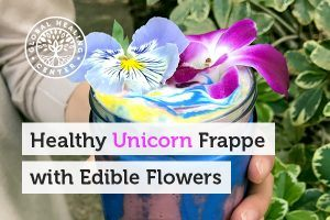 A glass cup of healthy unicorn frappe with edible flowers