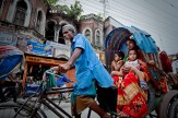 A mother on a rickshaw holds her children in Bangladesh.