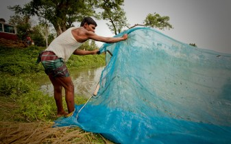 A man in Bangladesh prepares fishing nets.