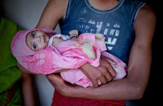 A man holds a baby with beautiful eyes in India.