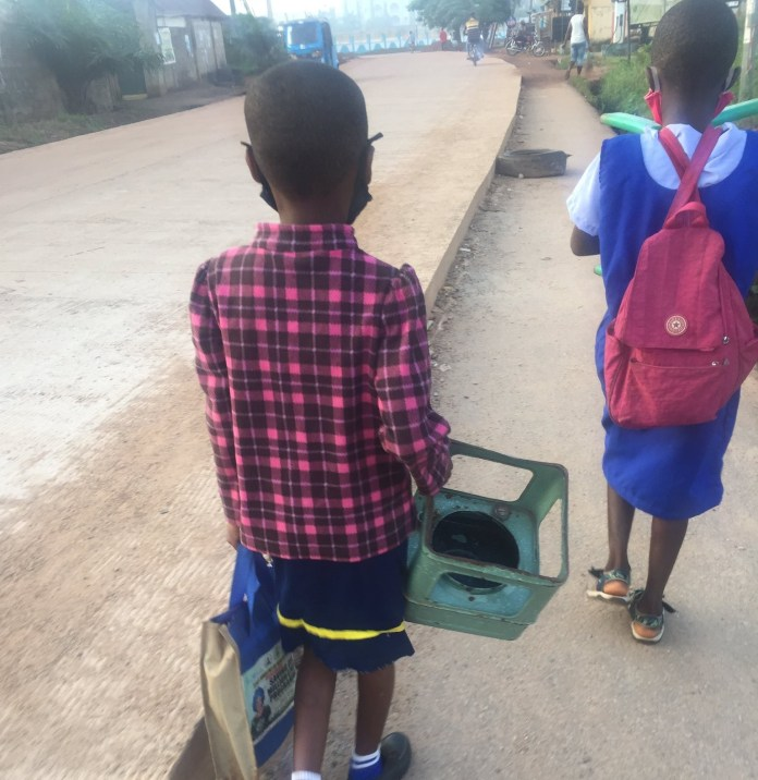 School girl captured on her way to school with a stove to be used as a chair in class