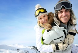 Cheerful snowboarder holding girlfriend on his back