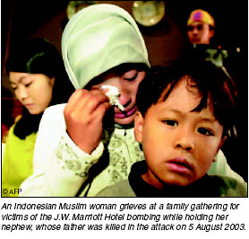 An Indonesian Muslim woman grieves at a family gathering for victims of the J.W. Marriott Hotel bombing, while holding her nephew, whose father was killed in the attack, 5 August 2003. [AFP photo]