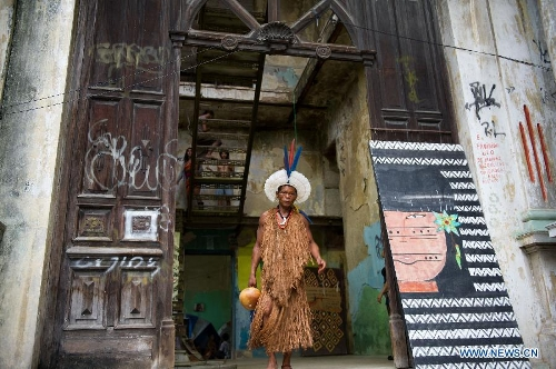 An indigenous man walks out of the old Indian Museum in Rio de Janeiro, Brazil, Jan. 16, 2013. The government of Rio de Janeiro plans to tear down an old Indian museum beside Maracana Stadium to build parking lot and shopping center here for the upcoming Brazil 2014 FIFA World Cup. The plan met with protest from the indigenous groups. Now Indians from 17 tribes around Brazil settle down in the old building, appealing for the protection of the century-old museum, the oldest Indian museum in Latin America. They hope the government could help renovate it and make part of it a college for indigenous Indians. (Xinhua/Weng Xinyang)