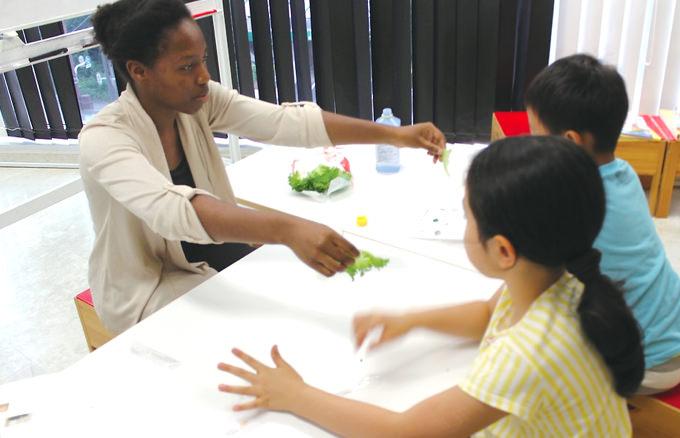 igsZ:ハーバード大卒のNaomi Wills先生。言語とともに異文化などを教えることを得意とし子供達と英語で対話しながらクラスが進められる。