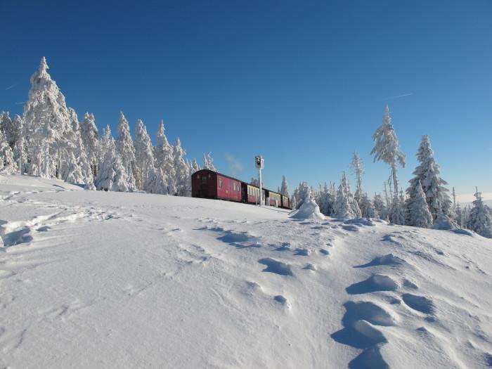 Wie ein bunter Blitz in der weiß-blauen Landschaft – die kleine Schmalspurbahn.