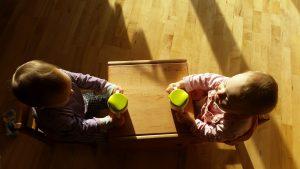 Kinder sitzen auf kleinen Sesseln an einem Tisch