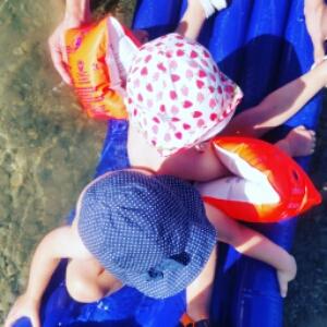 Kinder auf einee Luftmatratze im Wasser.