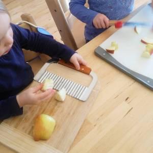Kleinkind schneidet Erdäpfel