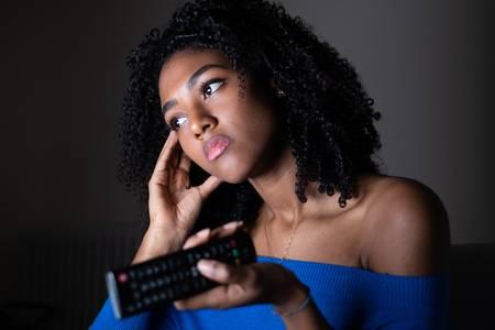 119078158-bored-black-woman-watching-television-at-night