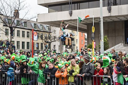 A happy Irishman watching the parade from a light pole.
