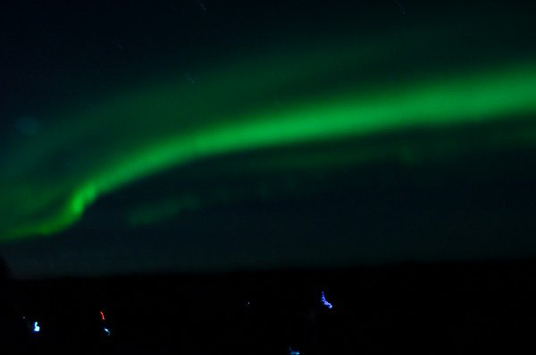 The majestic northern lights shining over the Icelandic countryside.