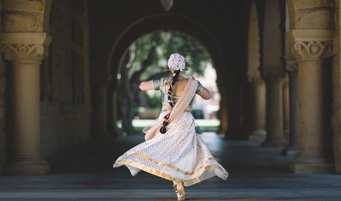 girl walking under arches