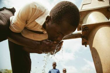 boy drinking water from a faucet in Uganda