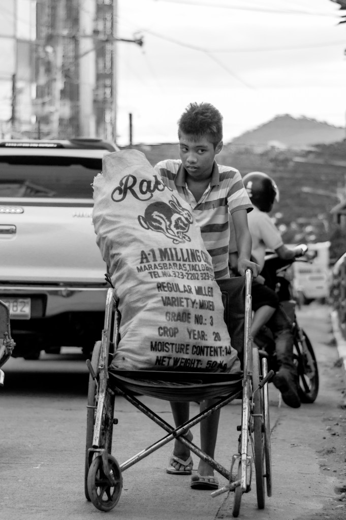 """PWD - person with determination"" - A mentally disabled boy gathers plastic bottles with his wheelchair. Photo Credit: Vic Gloria"